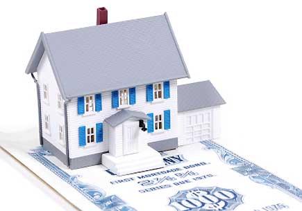 Miniature house on a mortgage bond. (stock image)