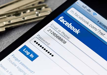 Facebook login page on iPhone display, keys in background. (stock image)