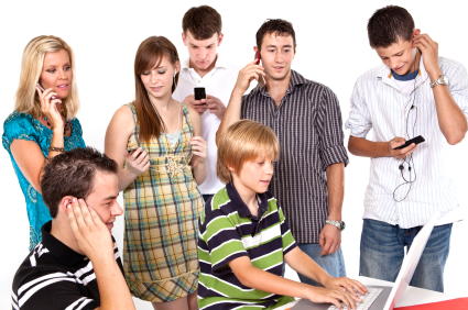 A group of busy teens on the phone and computer. (stock image)