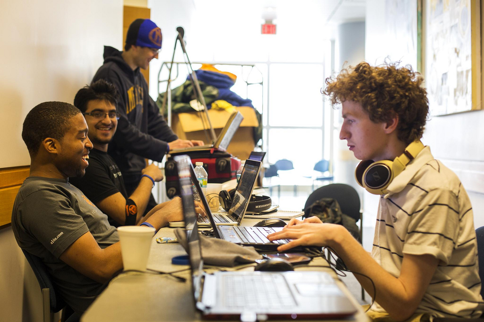 Alexander Biggs (right), of the University of Toronto, and Rashad Russel and Miker Angalz, of the University of Illinois-Urbana Champaign, work in a hallway in the Palmer Commons during the hackathon. Image Credit: Joseph Xu