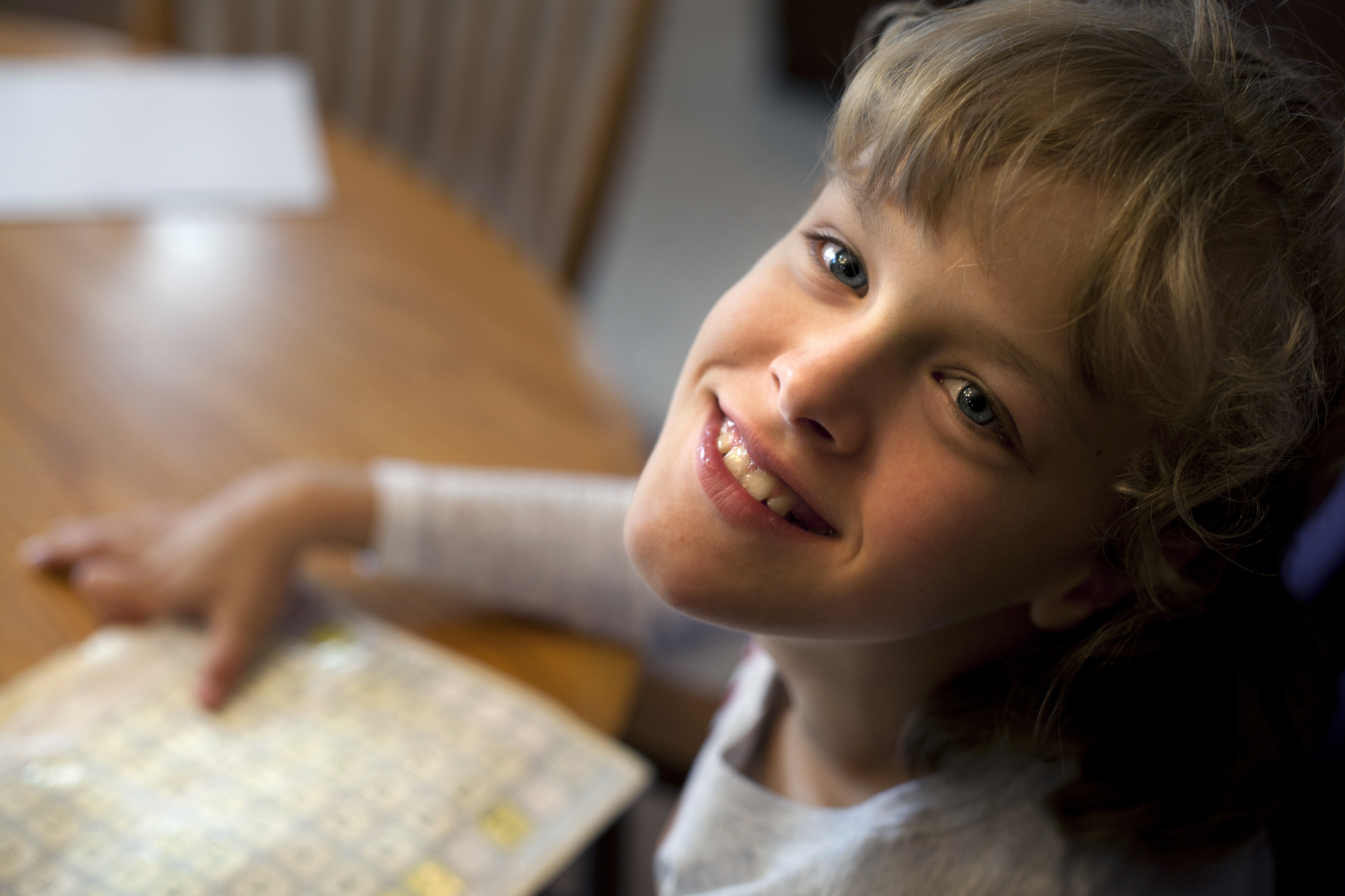Sitting by the dining table in her parents' Westphalia, MI house, Grace smiles to the photographer. Her hand rests on a board with letters and numbers she uses to communicate. Image credit: Marcin Szczepanski