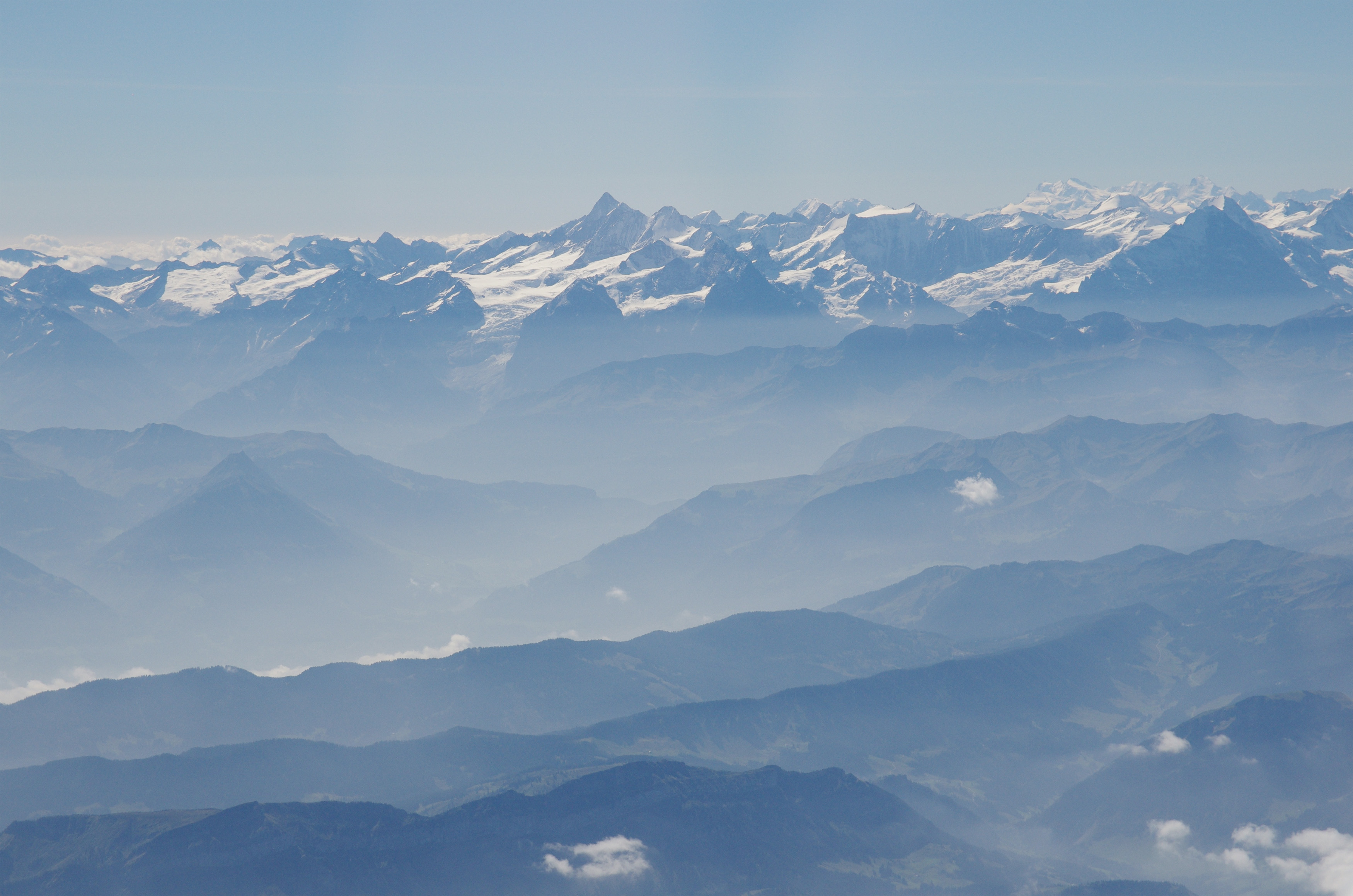 This photo from summer 2012 shows how air pollution in the Alps tends to be confined to lower altitudes, concentrating the deposition of soot and dust on the lower slopes. At center left in this picture, a glacier can be seen extending from a high altitude snow field, above the pollution layer, down into the valley where its lower reach is bathed in pollutants. Image credit: Peter Holy