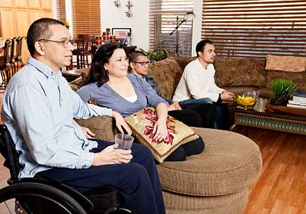 Man in a wheelchair watching television with family. (stock image)
