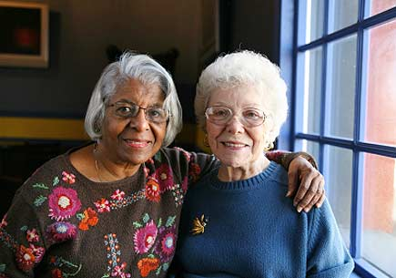 Two senior women embrace in front of a window. (stock image)