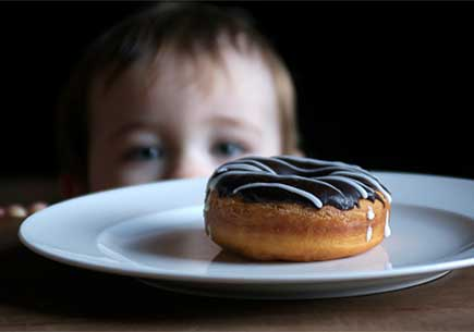 A child looks longingly at a donut just out of reach on the table. (stock image)
