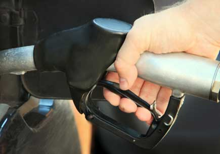 A hand holding a gasoline nozzle fills up a gas tank. (stock image)