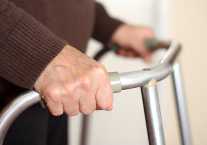 Close-up image of a senior citizen's hands on a walker. Image credit: Flickr.com user SalFalko