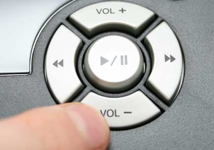 A finger presses the lower volume button. (stock image)