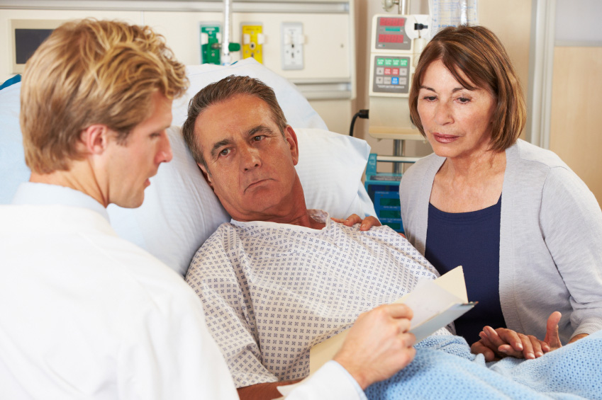 A doctor meets with a couple at the hospital. (stock image)