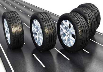 Digital rendering of five tires rolling on a strip of road. (stock image)