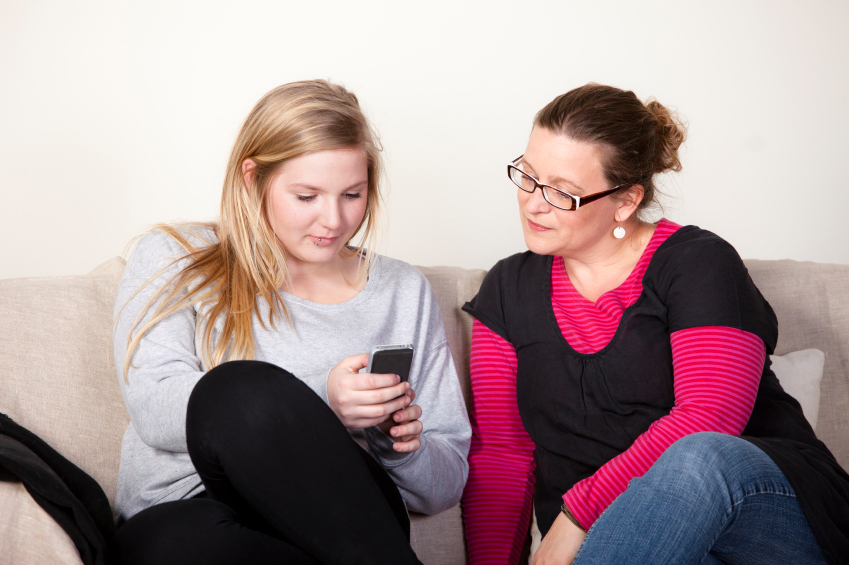A mother and daughter use a cell phone together. (stock image)