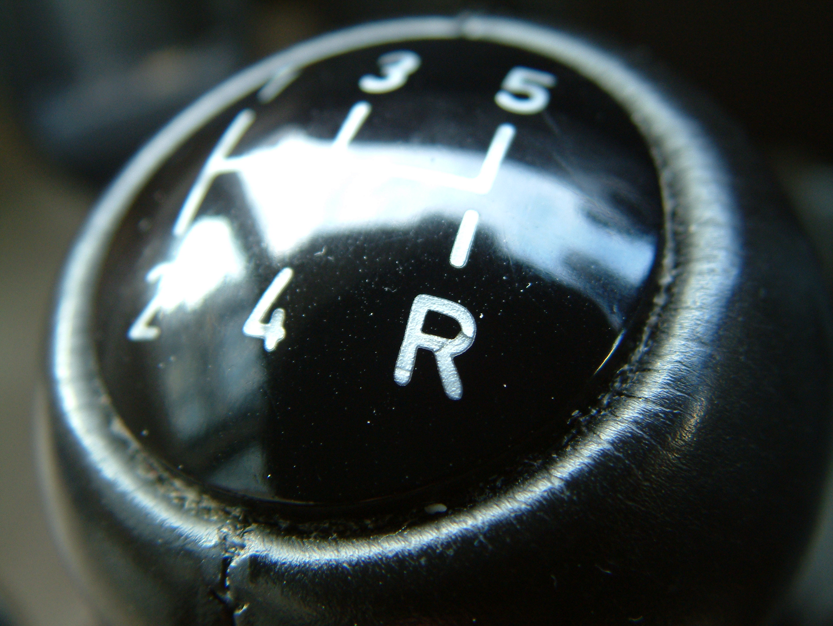 Automobile gear shifter knob with R (Reverse) in focus. Image credit: sxc.hu user myles