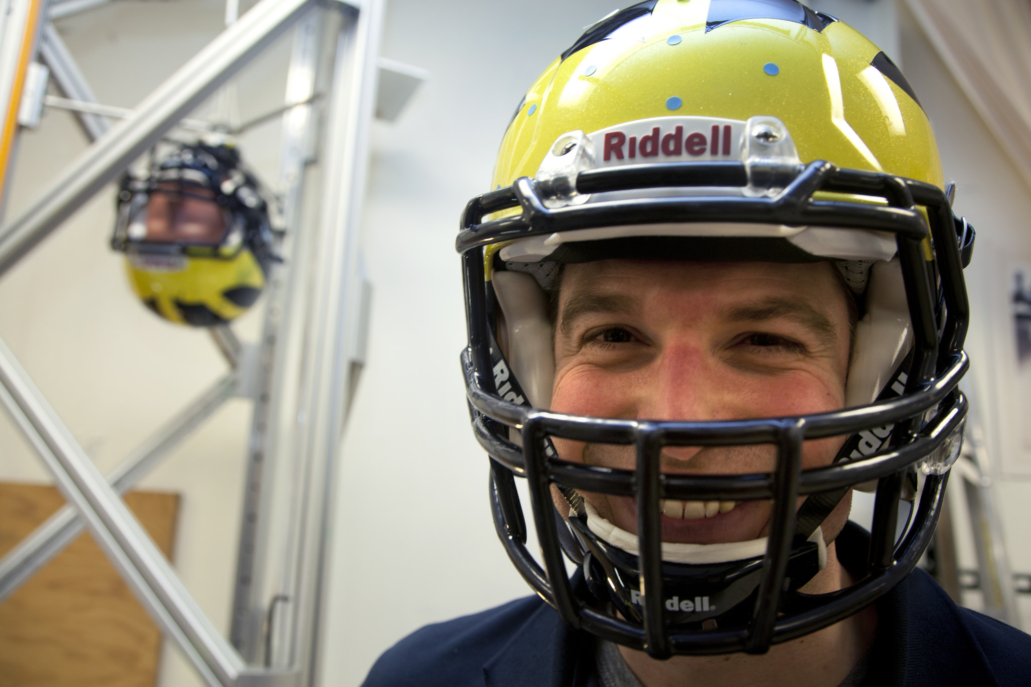James Eckner, assistant professor of Physical Medicine and Rehabilitation poses in a Michigan football helmet as he gets ready to test helmet collision on a crash test dummy. Researchers in the Biomechanics Research Lab in the Department of Mechanical Engineering test new sensors that are designed to tell players and their coaches how hard they're hit. Such information can help in concussion diagnosis. Photo by Marcin Szczepanski, Michigan Engineering