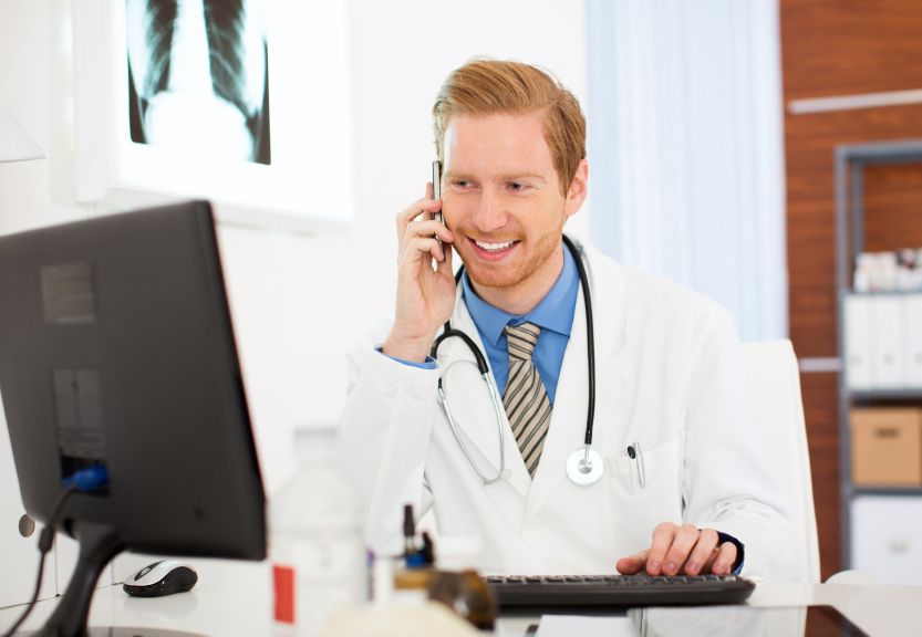 A doctor on the phone and looking at a computer screen. (stock image)