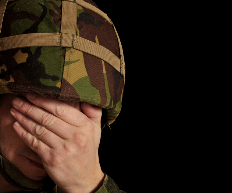 A soldier covers his face with his hands. (stock image)
