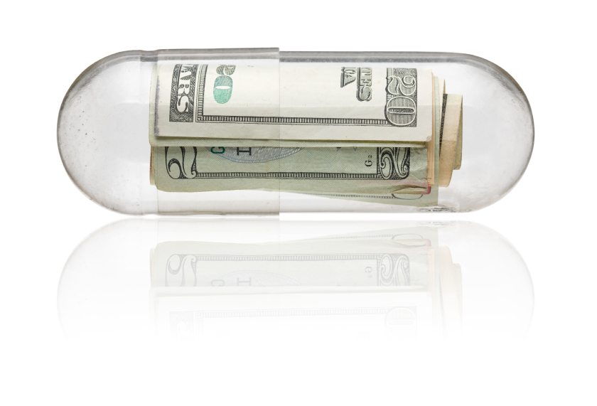 Several twenty-dollar bills rolled up and encased in a medication capsule. (stock image)