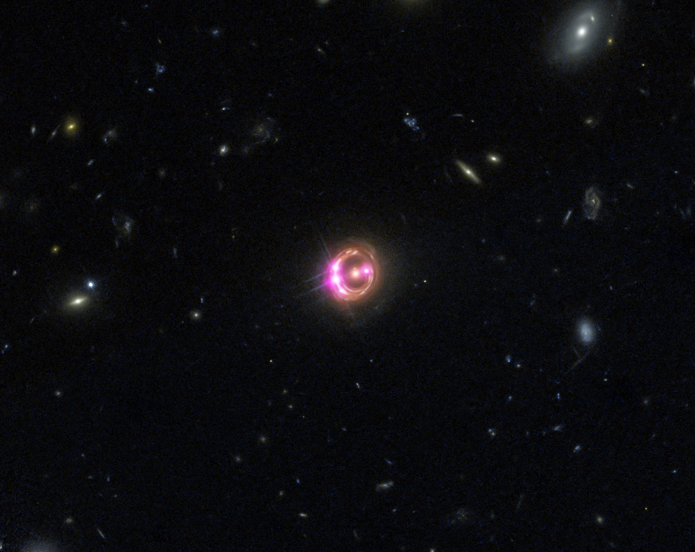Multiple images of a distant quasar are visible in this combined view from NASA's Chandra X-ray Observatory and the Hubble Space Telescope. The Chandra data were used to directly measure the spin of the supermassive black hole powering this quasar. Credit: X-ray: NASA/CXC/Univ of Michigan/R.C.Reis et al; Optical: NASA/STScI