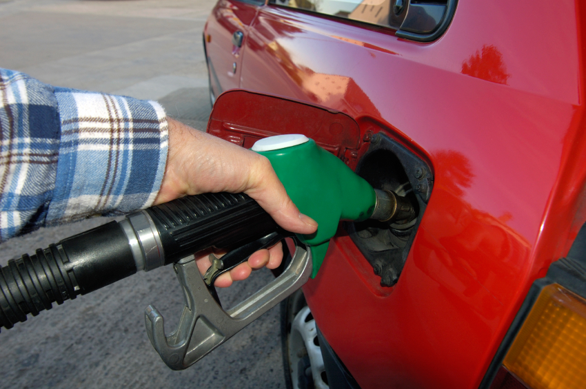 A hand on a gas pump filling up a car's gas tank. (stock image)