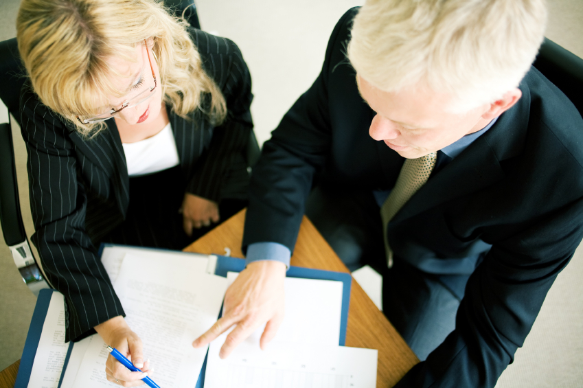 Overhead view of two business professionals examining documents. (stock image)