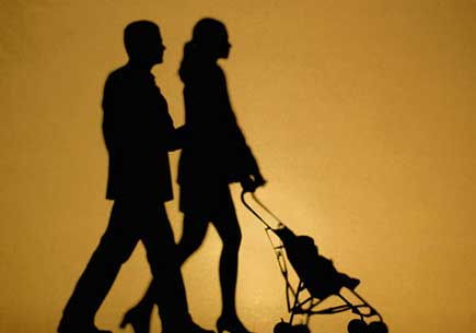 Silhouette of a couple walking with a baby stroller. (stock image)