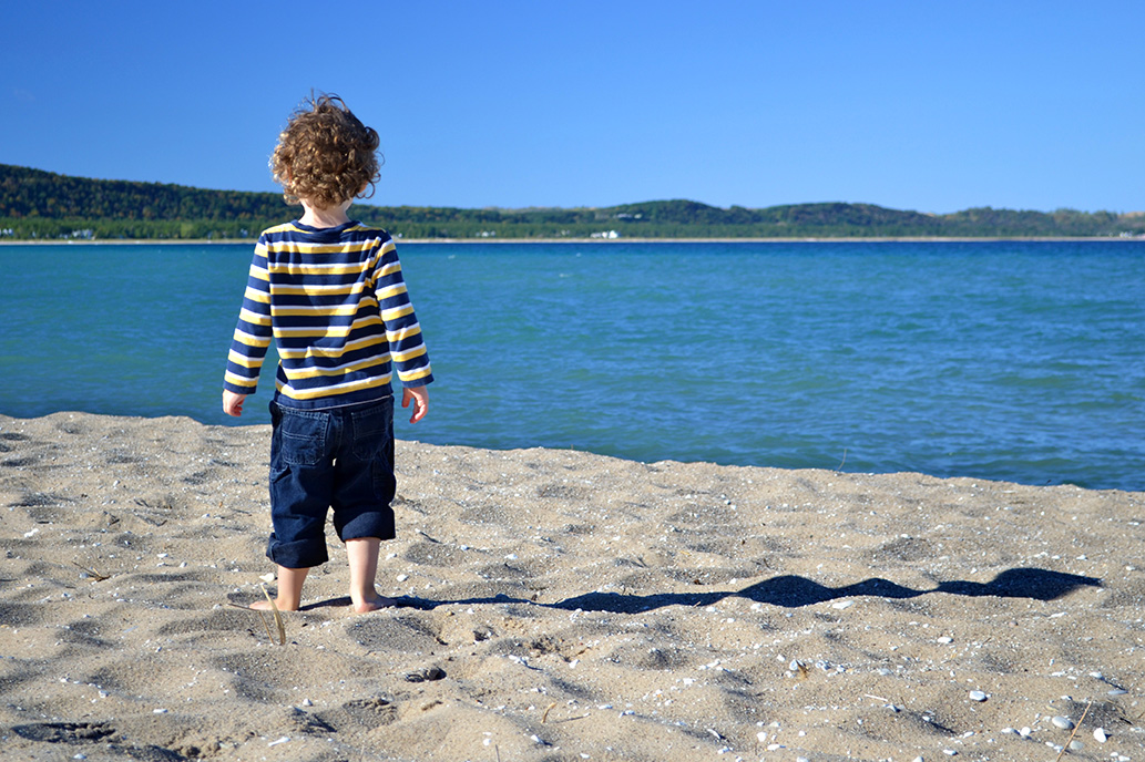 A young child stands on a beach looking out at one of the Great Lakes. Image credit: Michigan Sea Grant