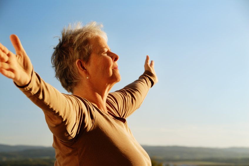 A senior woman embraces the world. (stock image)