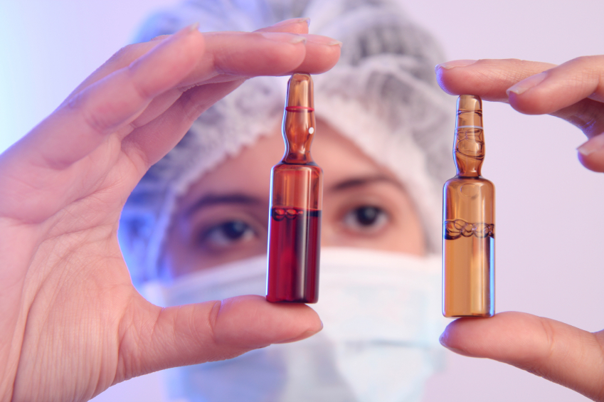 A researcher compares two vials of medication. (stock image)
