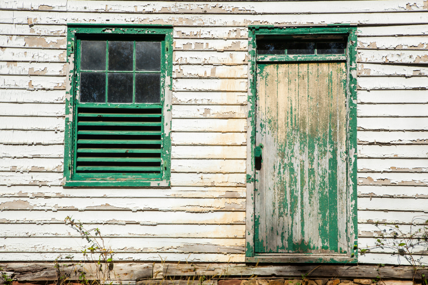 Exterior of a house with peeling paint and an old window and door. (stock image)