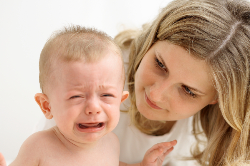 Mother calming crying baby. (stock image)