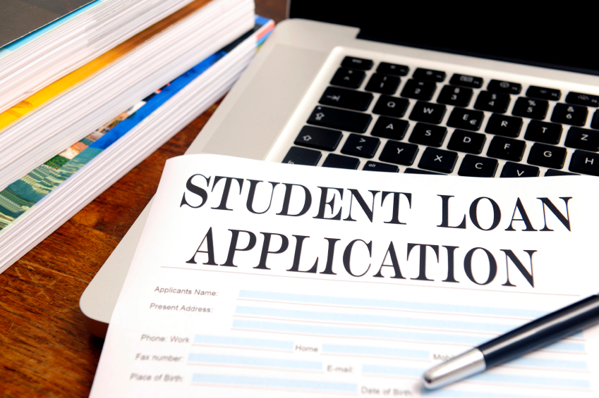 blank student loan application on desk with pen, books and laptop. (stock image)
