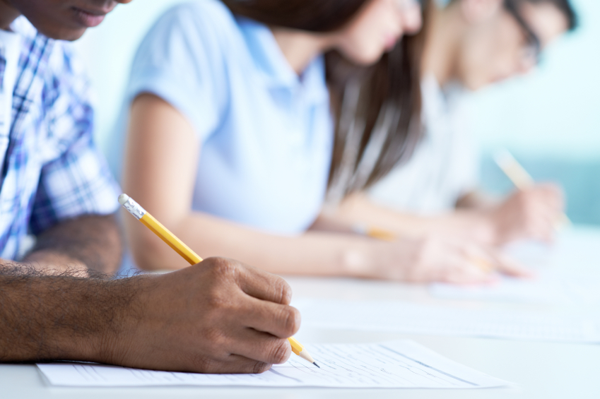 A tightly cropped photo of students writing. (stock image)