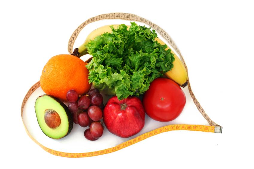 Frutas e vegetais frescos cercado por um coração em forma de fita métrica no fundo branco. (imagem)