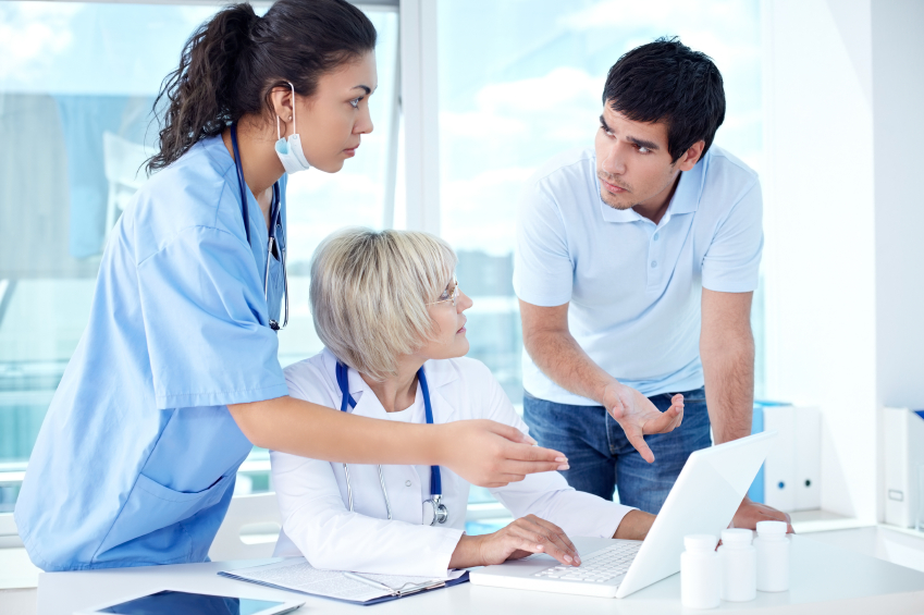 A patient, doctor, and nurse discuss a patient's electronic medical records. (stock image)
