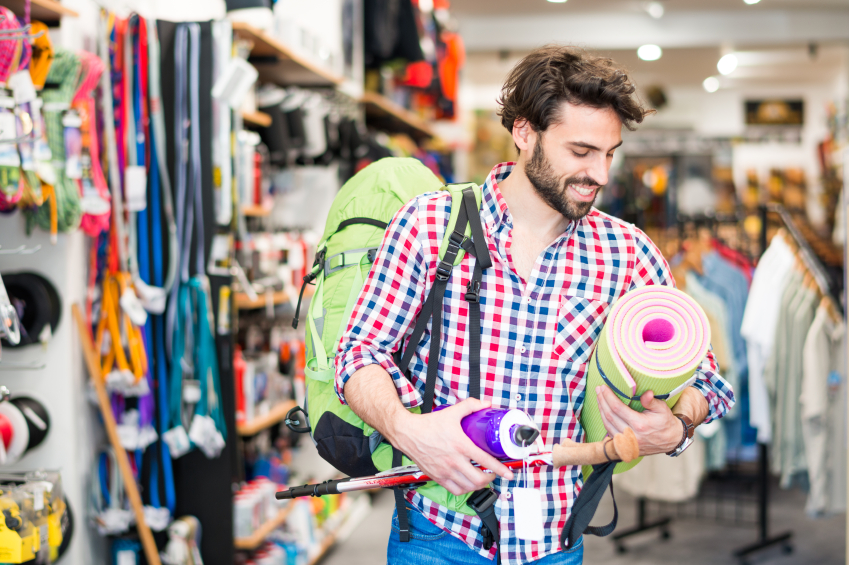 Man in sports goods store buying items for outdoor activities. (stock image)