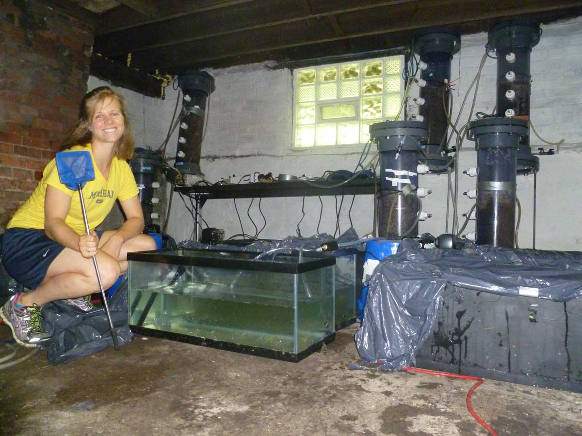 Lizzie Grobbel with the equipment used to grow shrimp in the basement of an unoccupied Detroit home. Image credit: Lizzie Grobbel