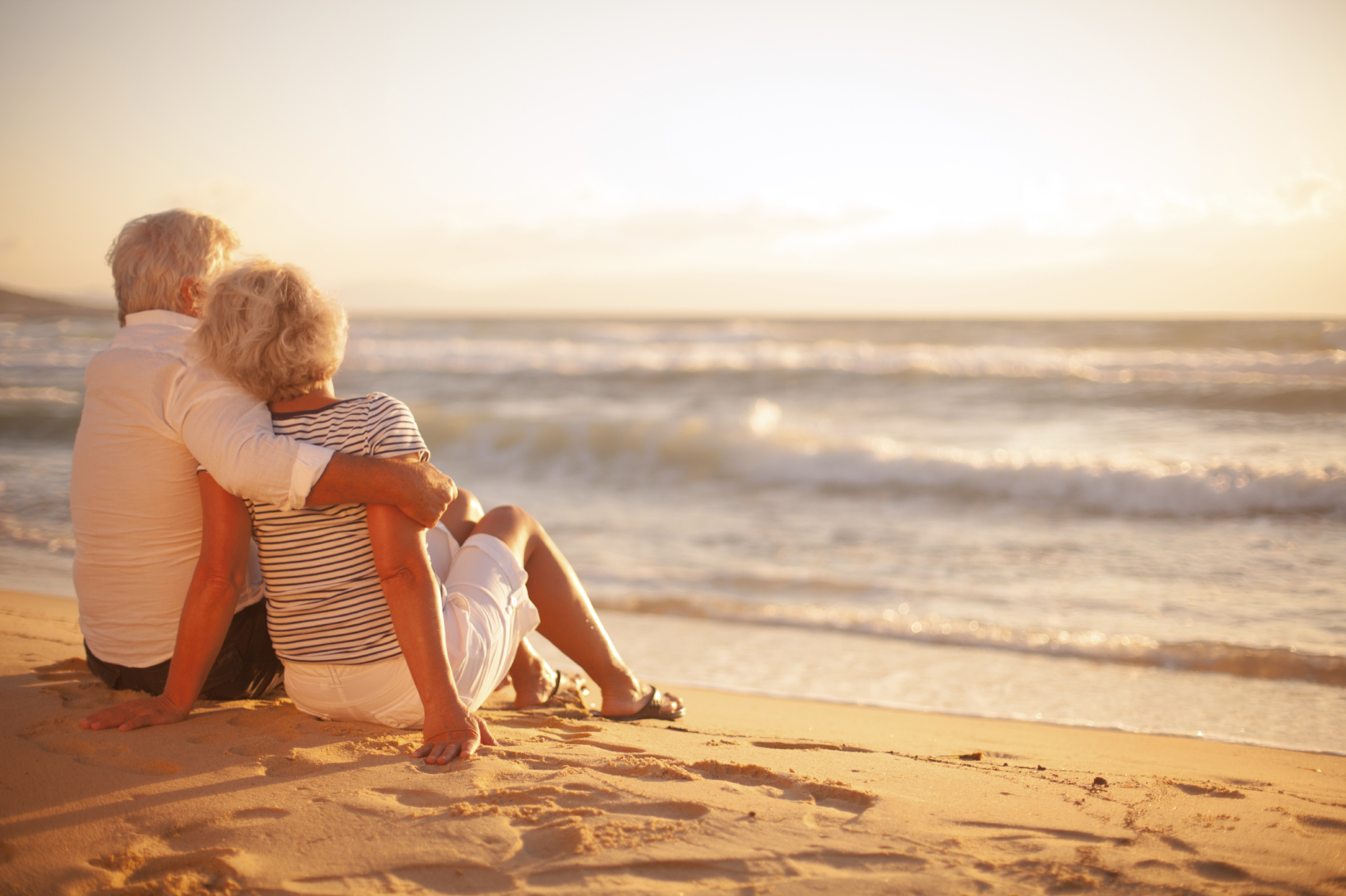 Older couple sitting on a beach during sunset. (stock image)