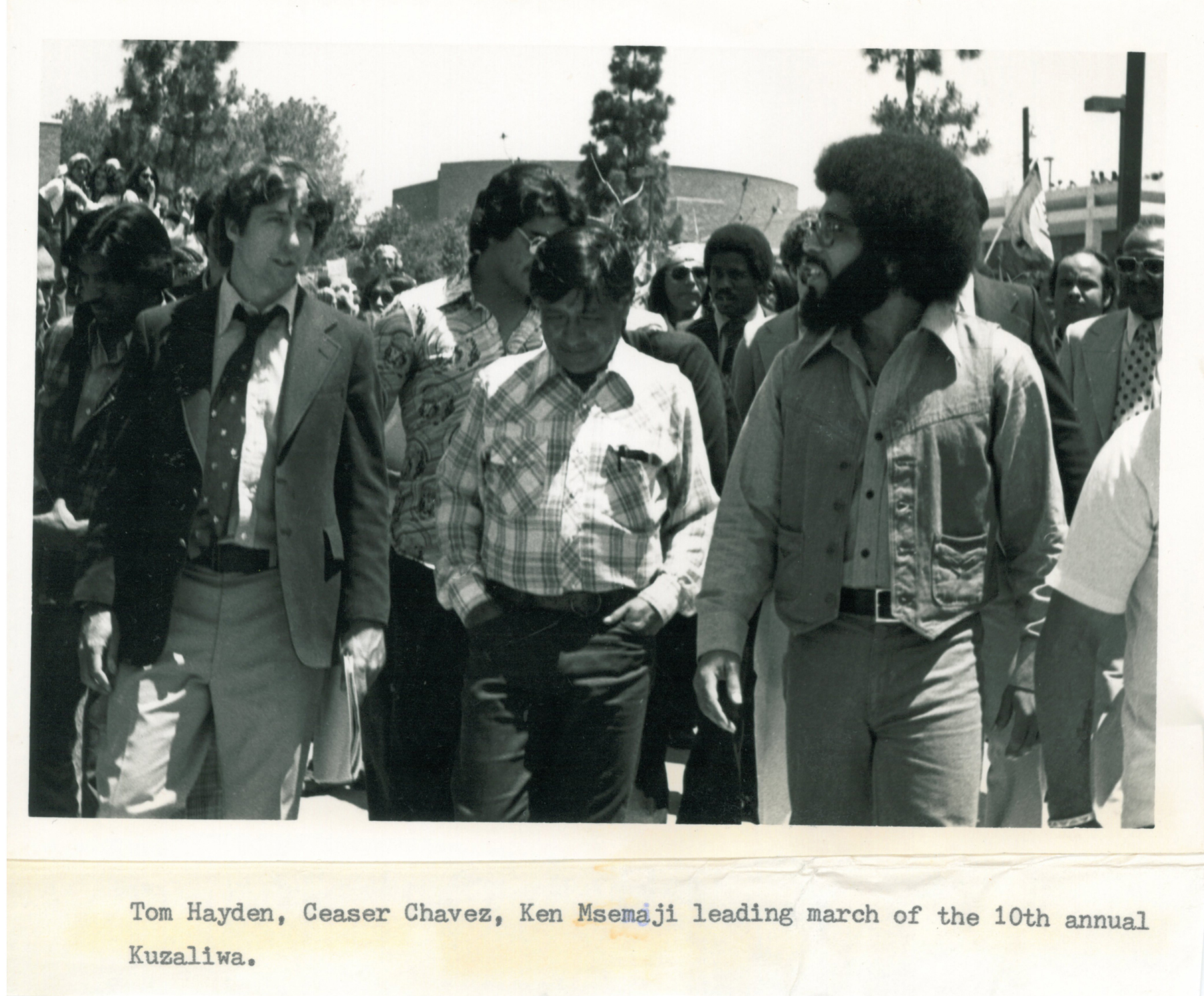 (From left): Tom Hayden, Cesar Chavez (United Farmworkers Union), and Ken Msemaji  (Nia Cultural Organization) leading the march of the 10th annual Malcolm X Kuzaliwa (birthday)   celebration, May 1977. Image credit: Tom Hayden Papers held at the University of Michigan Library