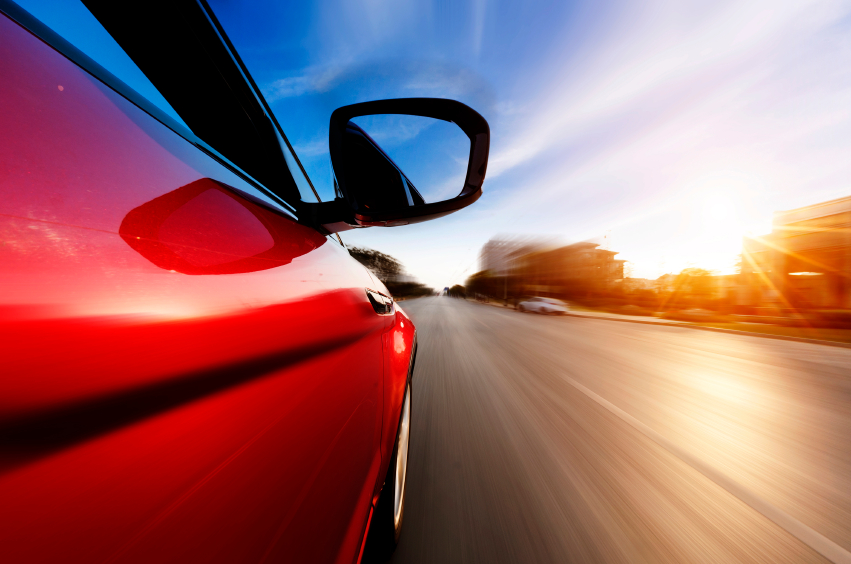 Red car speeds along a road. (stock image)