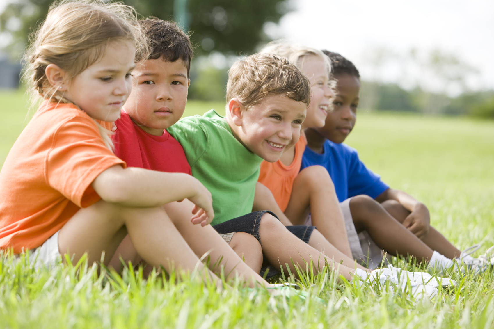 A group of preschoolers sits together outside. (stock image)