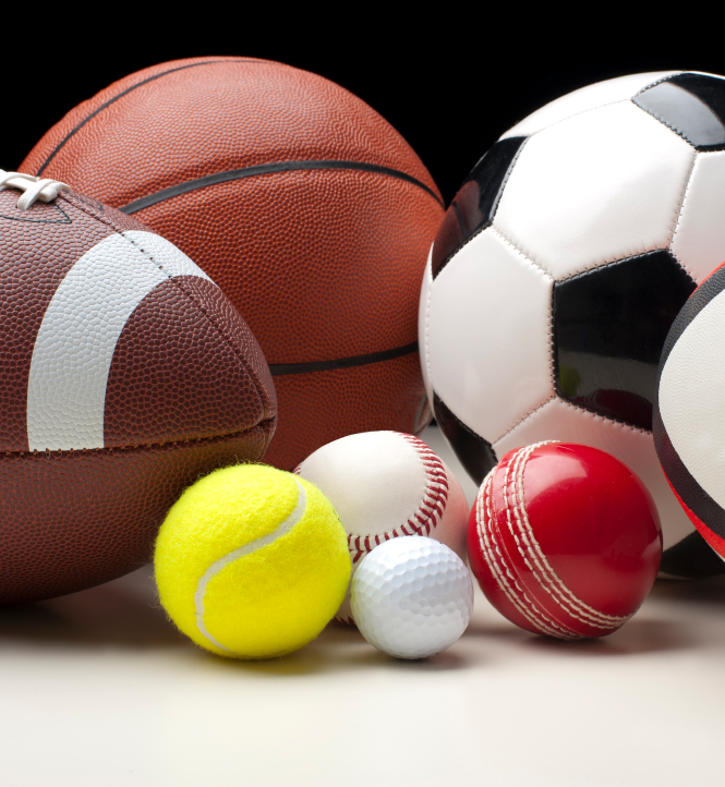 A football, basketball, tennis ball, golf ball, soccer ball, and rugby ball sitting on a table. (stock image)