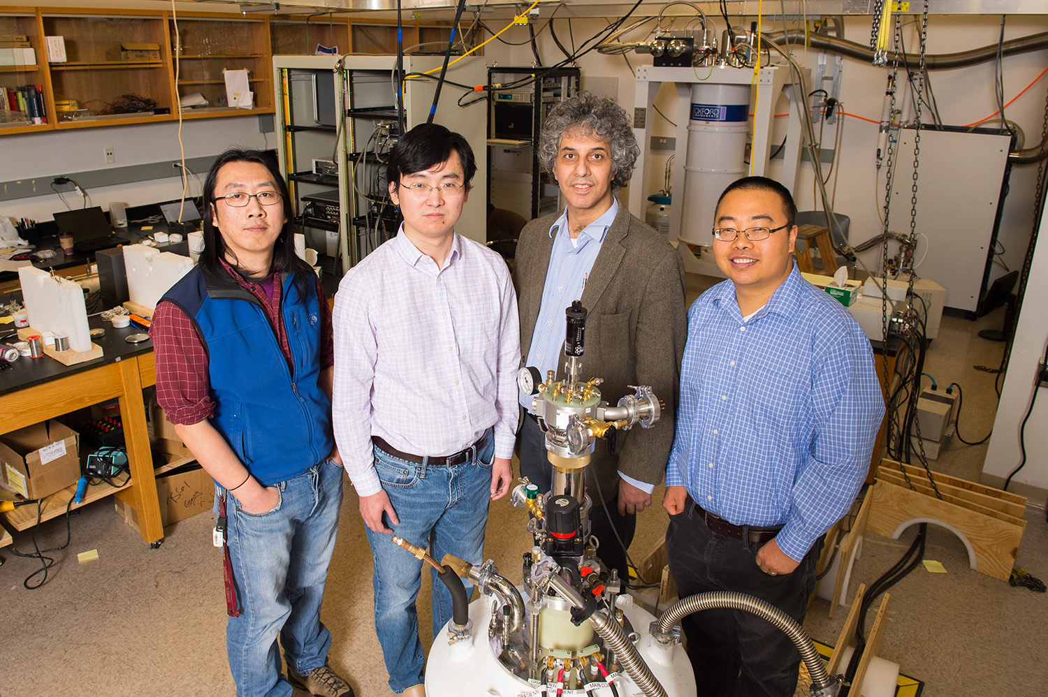 Physics researchers at the University of Michigan have confirmed the strange electrical behavior of a material called samarium hexaboride. The compound, it turns out, is a topological insulator. Gang Li, postdoctoral researcher; Kai Sun, assistant professor; Cagliyan Kurdak, professor; and Lu Li, assistant professor, stand in front of their experimental set-up. Image credit: Daryl Marshke, Michigan Photography