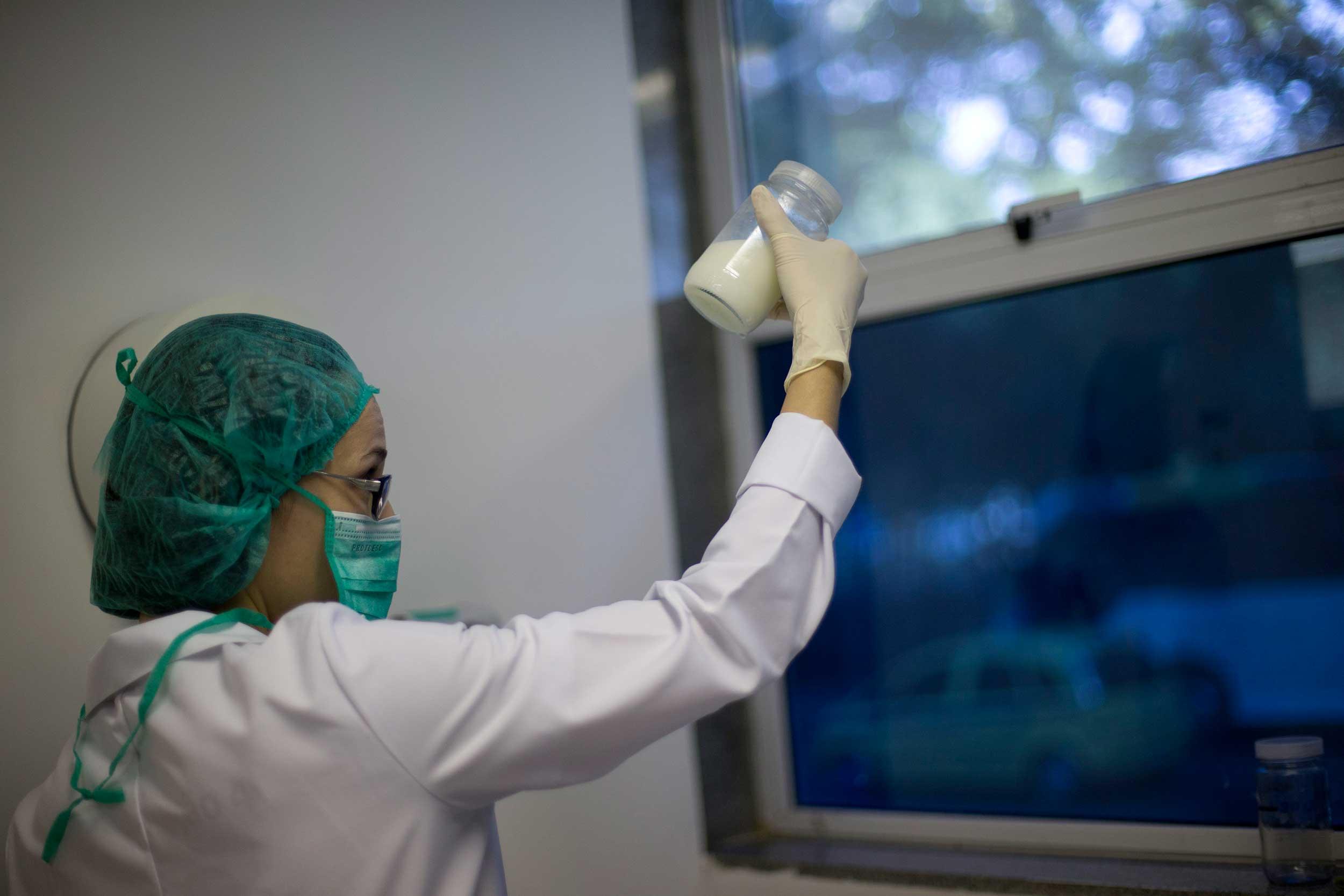 A Brazilian milk bank worker examines a donation of breast milk. (AP Photo/Silvia Izquierdo)