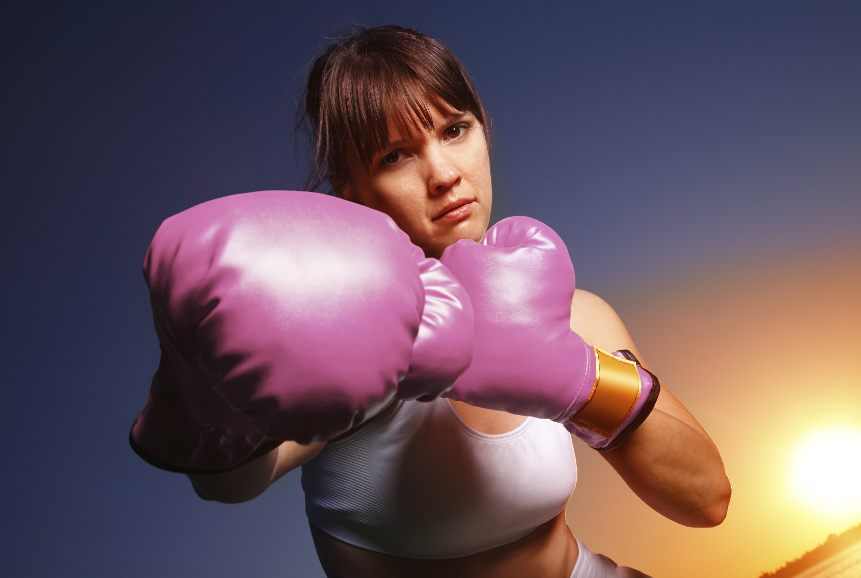 A woman wearing pink boxing gloves metaphically fights cancer. (stock image)