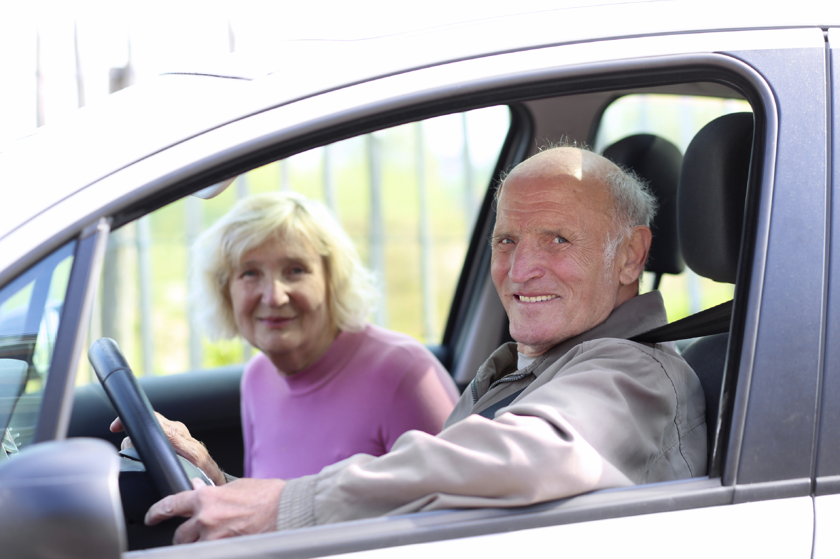 Happy senior couple driving modern car. (stock image)