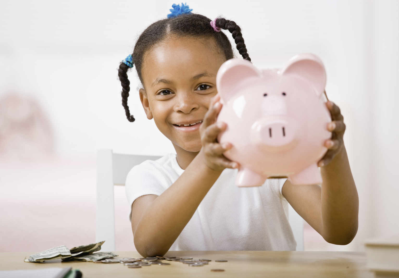 A young girl proudly holds up her piggy bank. (stock image)