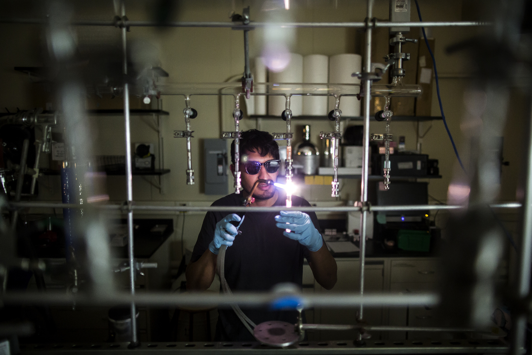 MSE PhD student Juan Lopez cuts a glass tube used in the production process for a new semiconductor compound in the HH Dow building. Image credit: Joseph Xu