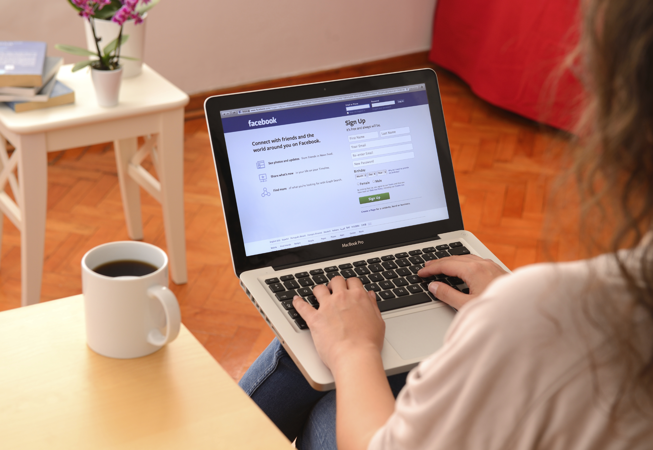 Over shoulder view of woman using Facebook on a laptop computer. (stock image)