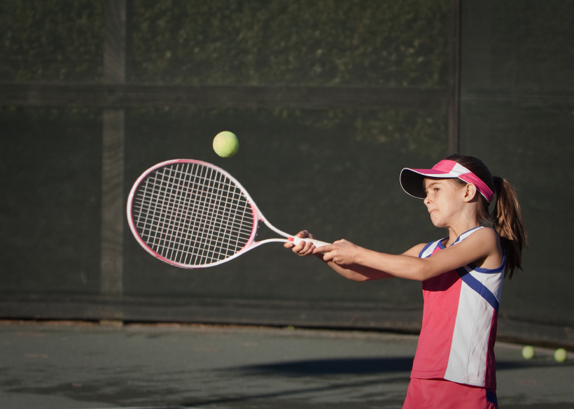 A young girl playing tennis. (stock image)