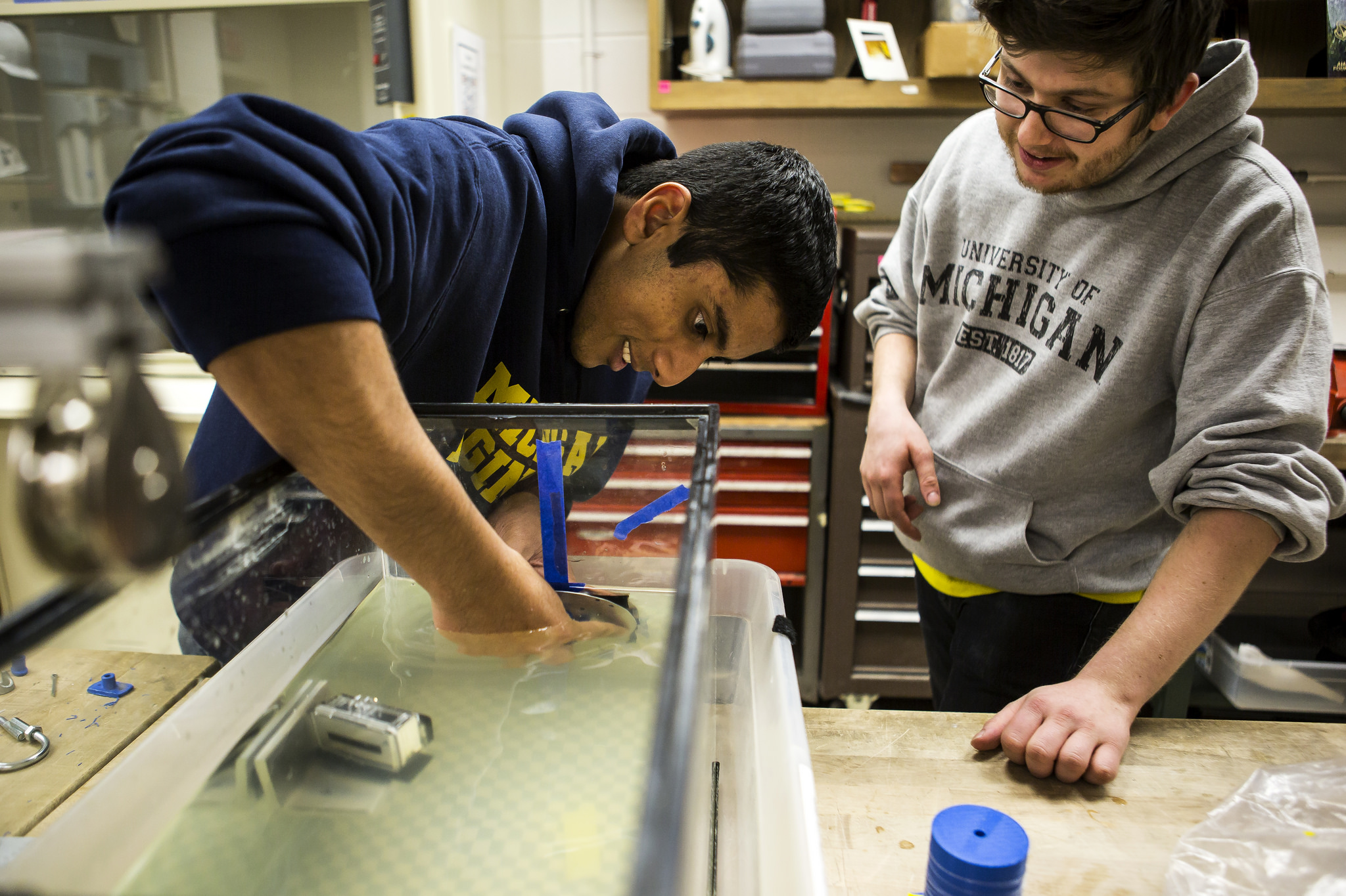 Siju Varughese, EE BSE Student, helps Steve West, AERO BSE Student, test the structure of small scale satellites (pico and femto sats) in the Space Research Building. Image credit: Joseph Xu, Michigan Engineering