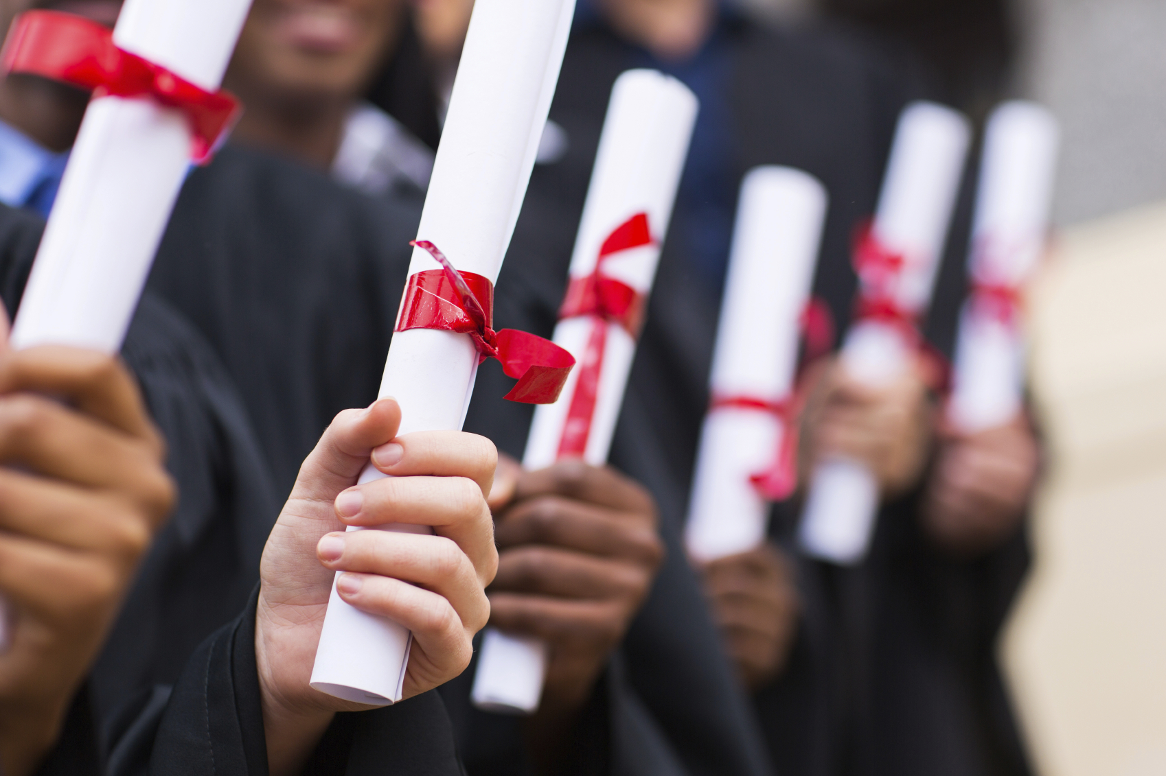 A group of graduates holding diploma. (stock image)